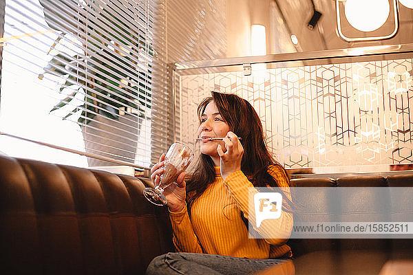 Fröhliches Teenager-Mädchen genießt Schokoladen-Milchshake  während sie im Café sitzt