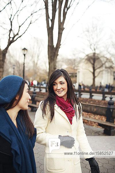 Freunde spazieren und unterhalten sich im Winter im Stadtpark