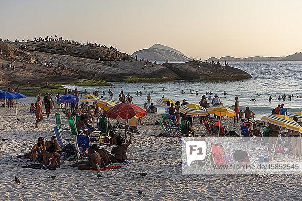 Menschen  die während des Sonnenuntergangs am Strand von Ipanema Beach baden  Atlantik