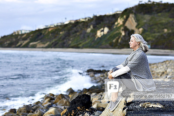 Seitenansicht einer älteren Frau mit geschlossenem Redaktionsraum  die bei Sonnenuntergang auf einem Felsen am Manhattan Beach sitzt