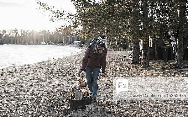 Frau  die im Winter am Strand einen Wasserkocher auf ein Feuer im Freien stellt