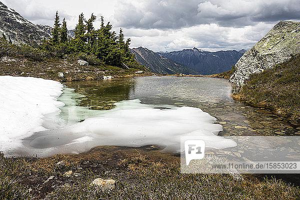 Der letzte Schnee und das letzte Eis schmilzt an einem Sommertag in den Bergen von Britisch-Kolumbien zu einem alpinen Becken.