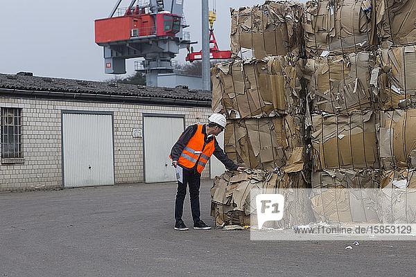 Arbeiter draußen  der sich um das Recycling von Papierverpackungen kümmert