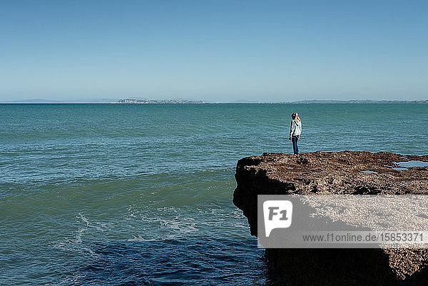 Mädchen steht auf einer Klippe mit Blick auf den Ozean