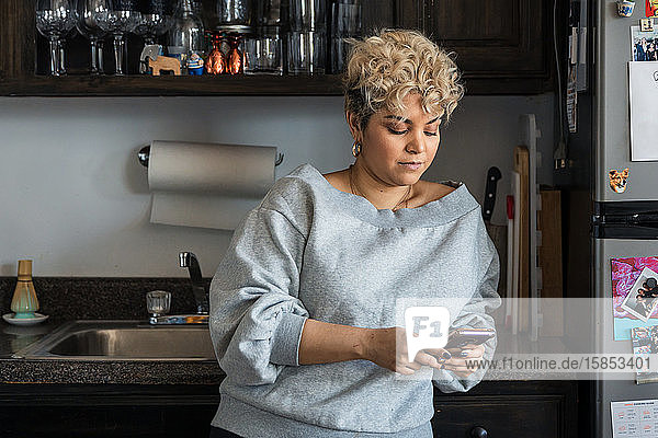 Woman with short hair text messaging on smart phone while leaning on kitchen counter at home