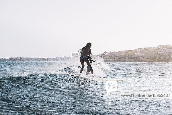Zurückgezogene Ansicht von Mutter und Sohn beim Surfen auf einer kleinen Welle auf See