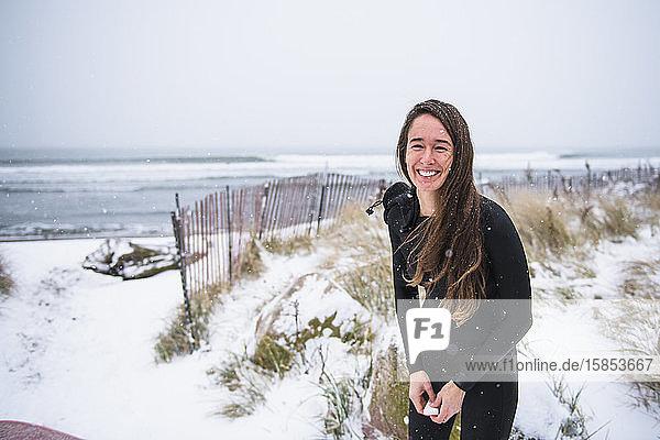 Frau lacht und geht im Winterschnee surfen