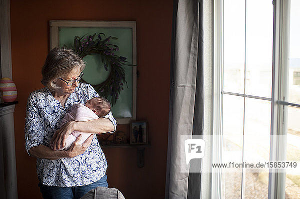 Grandmother holding newborn granddaughter by window at home