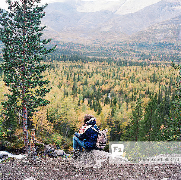 Beautiful woman sitting near the waterfall enjoying the sun