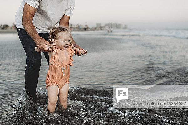 Toddler girl splashing in ocean with father at sunset