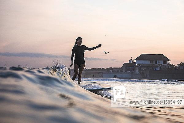 Wasserfreundinnen surfen gemeinsam bei Sonnenuntergang