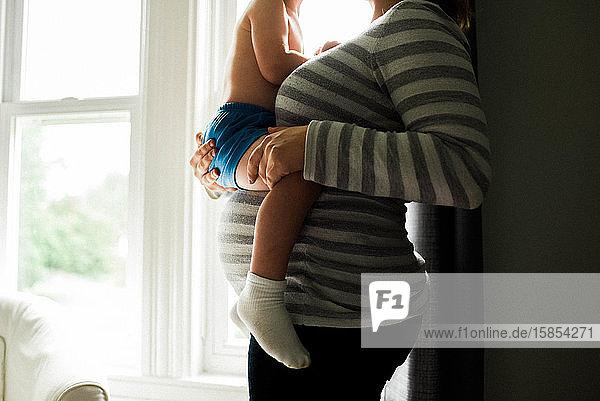 Eine werdende Mutter  die ihr Kleinkind über ihren Höcker hält.