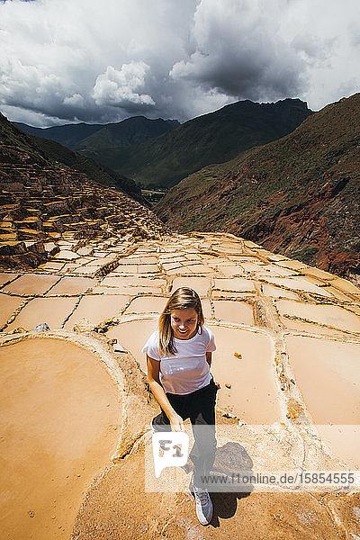 Junge Frau geht in der Nähe der berühmten Salzminen in Peru spazieren