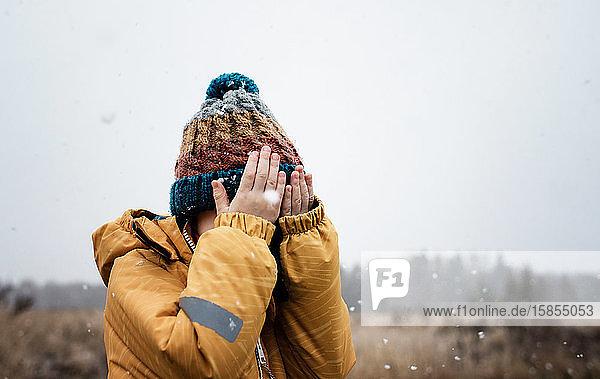 Junge  der beim Spielen im Schnee sein Gesicht mit den Händen bedeckt