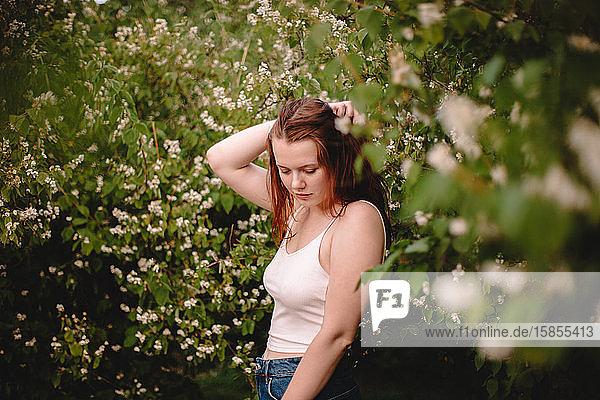 Junge Frau steht im Frühling inmitten blühender Zweige im Park
