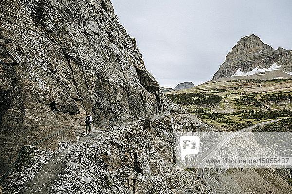 Wanderin wandert am Rande einer Klippe entlang  Highline Trail  Montana
