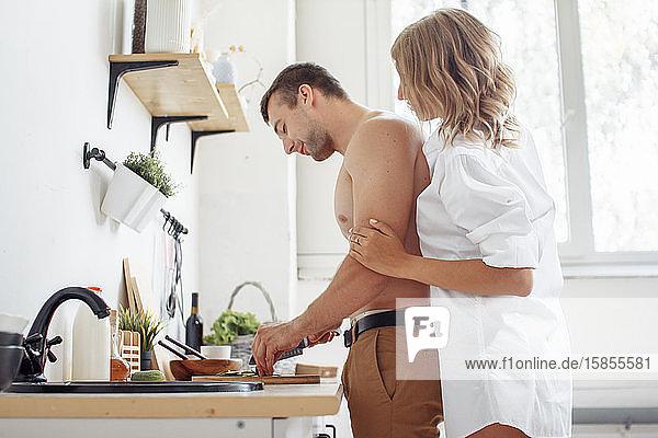Liebevolles  fröhliches Paar  das sich umarmt und gemeinsam in der Küche kocht