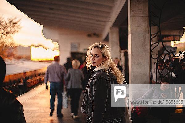 Junge Frau schaut zurück in die Kamera und geht in der U-Bahn-Station