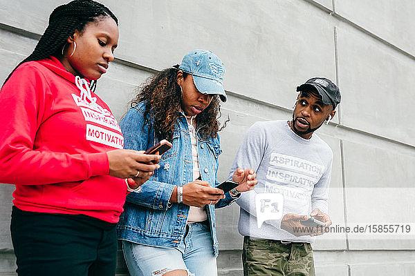 Städtische Freunde schauen sich Smartphones draußen an der Wand an