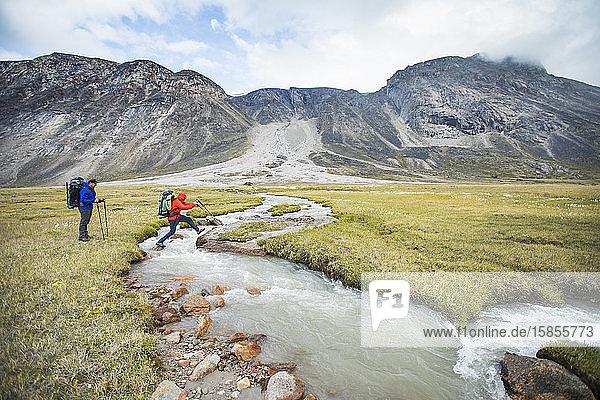 Rucksacktouristen überqueren den rauschenden Fluss an einer Engstelle  dem Akshayak-Pass.