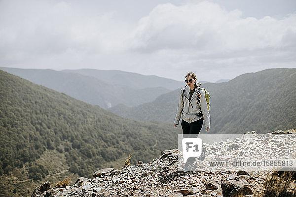 Female hiker walks trail in Kahurangi National Park  New Zealand