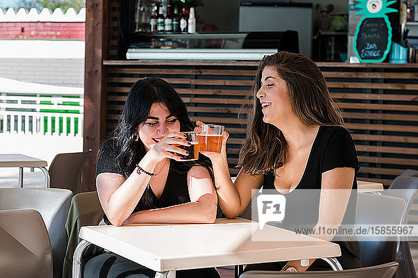 Two young women are drinking beer in a terrace of a pub. Lifestyle  leisure