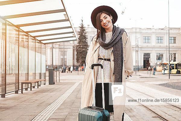 Stilvolles Mädchen mit einem Koffer steht an einer Stadthaltestelle und wartet auf eine Straßenbahn