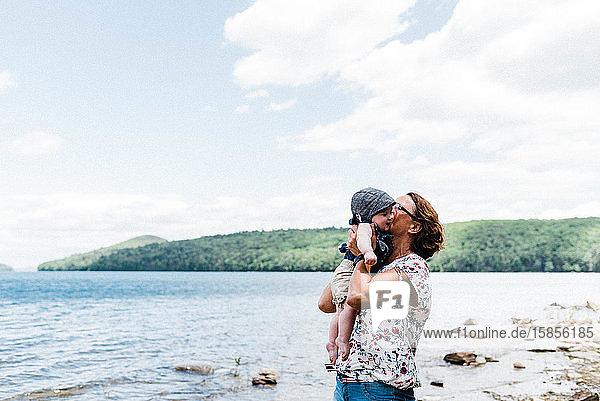 Großmutter küsst ihre Enkelin während einer Fahrt zum See.