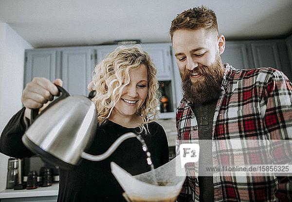 Ein lächelndes junges Paar lässt sich in seiner Küche Kaffee übergießen