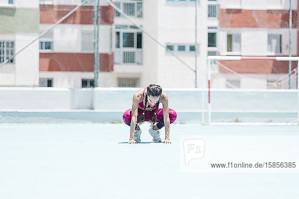 Farbenfrohes Bild des vollständigen Körpers einer Athletin  die auf dem Platz ruht