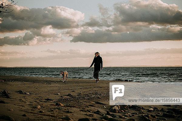 Frau beim Hundeausführen in der Abenddämmerung am Strand