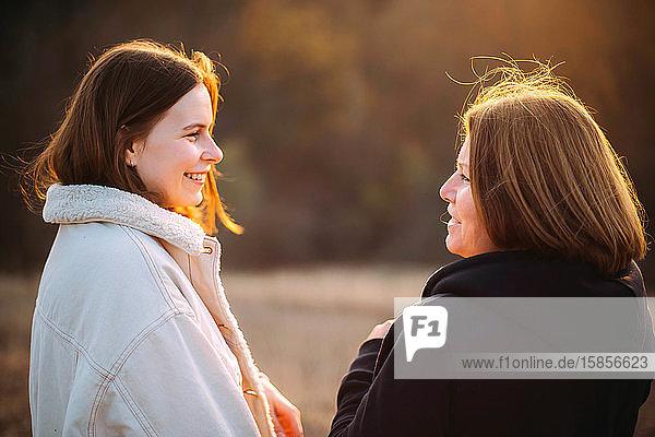 Nahaufnahme der glücklichen Mutter und Tochter bei Sonnenuntergang.