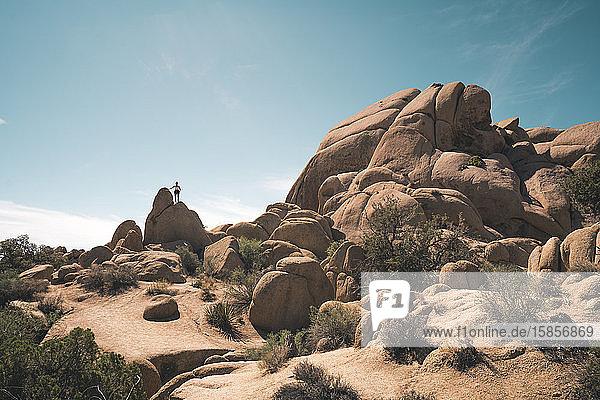 Frau klettert an surrealer Felsformation vor blauem Himmel