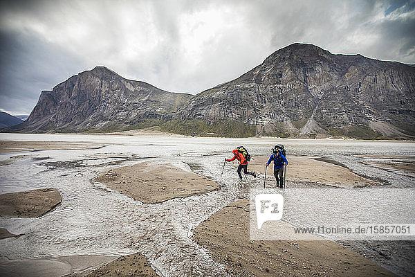 Zwei Rucksacktouristen befahren eine Reihe von Flussüberquerungen am Akshayak-Pass