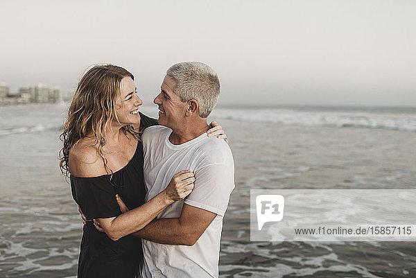 Seitenansicht eines Ehepaares  das sich im Meer betrachtet