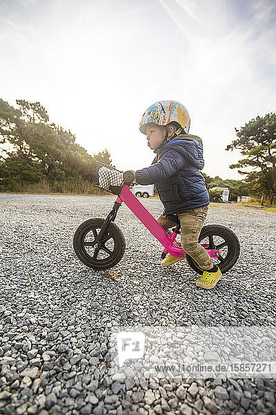 Side view of one year old girl on pink bike.