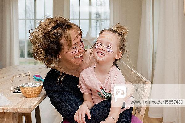 Mutter und Tochter lachend beim Verkleiden und Schminken zu Hause