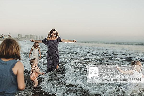 Starke Mutter mit vier Töchtern  die bei Sonnenuntergang im Meer spielen