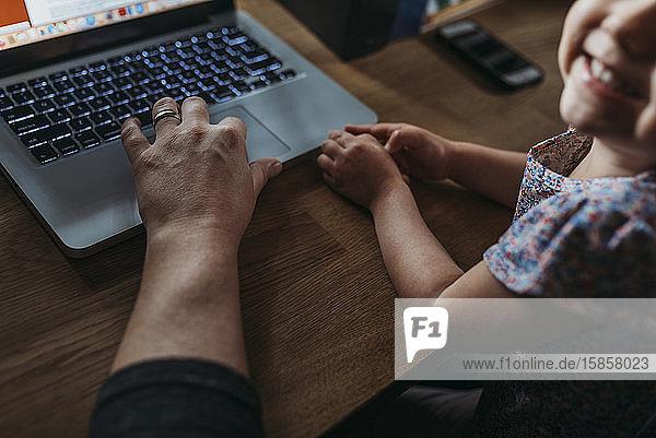 Nahaufnahme eines jungen Mädchens und eines Vaters  während er von zu Hause aus arbeitet