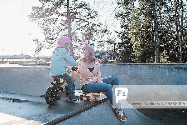 Frau  die mit ihrer Tochter in einem Skatepark draußen in der Sonne spielt