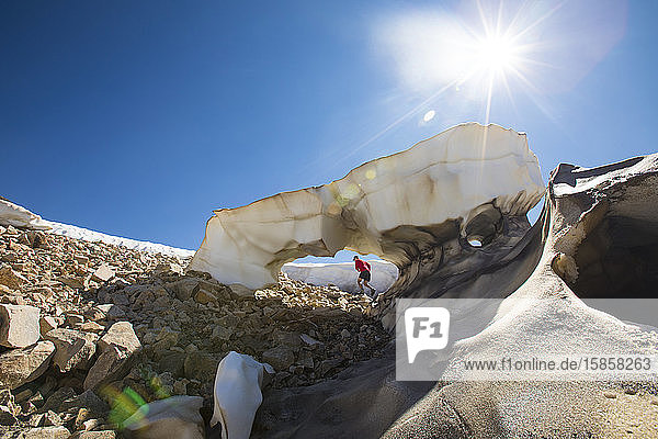 Low angle view of trail runner through melting glacier.