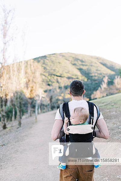 Ein junger Vater wandert  während er seinen Sohn auf dem Rücken trägt.