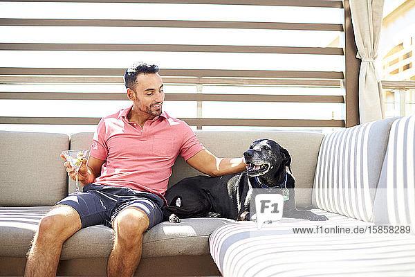 Ein Mann entspannt sich im Freien bei einem Drink und seinem Hund.