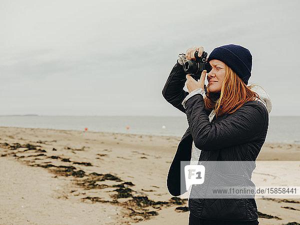 Frau fotografiert am Strand in Schottland