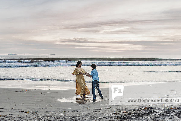 Landscape of mother and son playing at water's edge during sunset