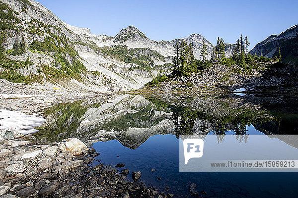 Panoramablick auf einen Berggipfel und seine Spiegelung auf einem See.