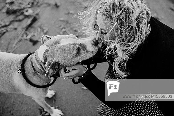 woman kissing her dog on the beach