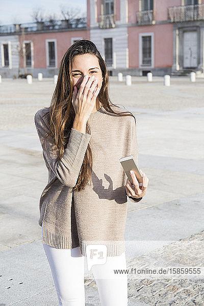 ein junges Mädchen  das sein Lächeln mit der Hand in boadilla del monte bedeckt