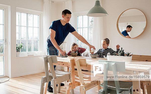 der Vater hilft seinen Kindern beim Frühstücken und bei den Vorbereitungen für die Schule