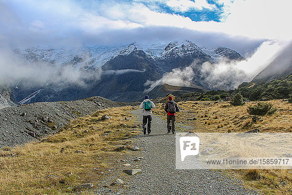 Two men hiking toward snowy mountains covered by clouds in New Zealand